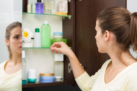shelves: Beautiful girl choosing beauty products from the bathroom cabinet