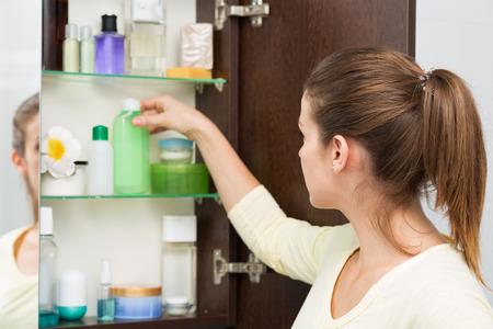 美しい女の子のバスルームのキャビネットから化粧品を選択します。 写真素材 - 44152572