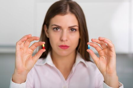 reliever: Pretty woman with a bottle of pills Stock Photo