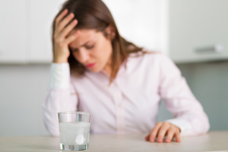 reliever: Glass of water with a dissolving pain reliever pill