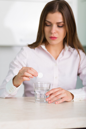 reliever: Woman puts a painkiller pill into a glass of water