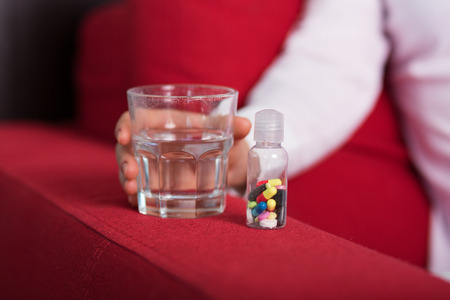 reliever: Glass of water with a bottle full of pills