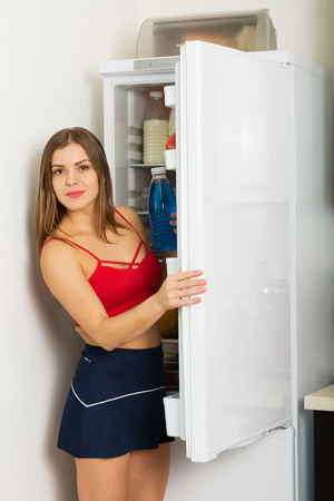 fridge: Woman standing by the fridge and choosing products Stock Photo