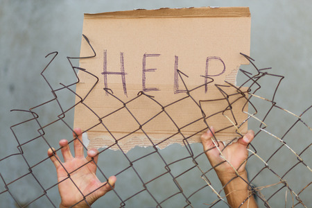 the borderline: A man standing behid the fence with a sign that reads 'Help!'