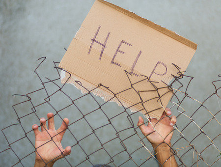 A man standing behid the fence with a sign that reads 'Help!'