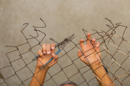 breaking down: A man breaking down the fence. Immigration concept Stock Photo