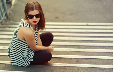 reckless: Lonely girl sitting on the stairs. Toned image Stock Photo