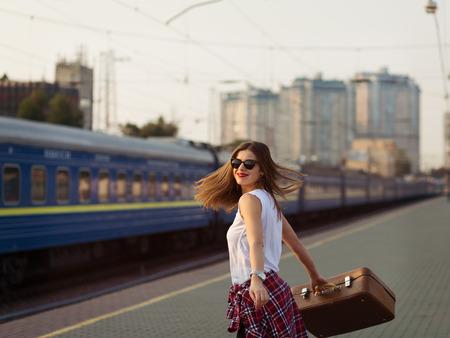 mujer con maleta: Woman waiting for a train. Retro toned image Foto de archivo