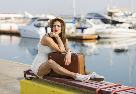 Young woman with a suitcase ready for a summer vacation