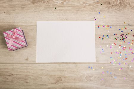 board desk: Gift box and colorful confetti on a wooden background Stock Photo
