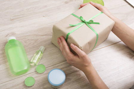 Gift box with green ribbon and cosmetics on a wooden background