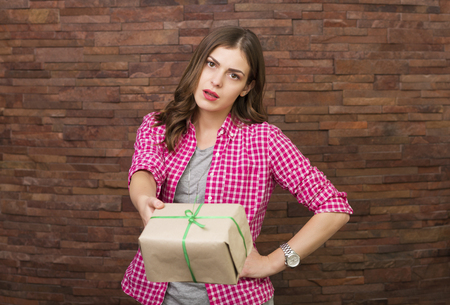 dissapointed: Beautiful annoyed woman opening a gift box Stock Photo