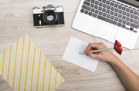 carta de amor: Ordenador portátil y una cámara en un fondo de madera