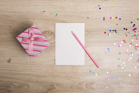 holiday celebration: Gift box and colorful confetti on a wooden background Stock Photo