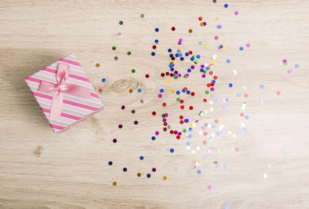Gift box and colorful confetti on a wooden background Foto de archivo