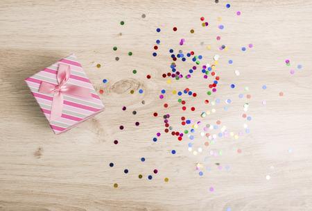 compleanno: Confezione regalo e coriandoli colorati su uno sfondo di legno