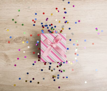 Gift box and colorful confetti on a wooden background Stock Photo