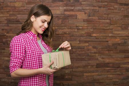 ladrillo: Mujer hermosa que abre una caja de regalo