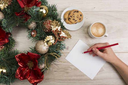 writing board: Coffee and a chocolate chip cookies with a Christmas decor on the wooden background