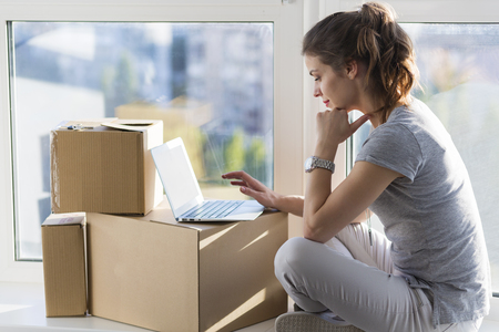 moving box: Beautiful girl moving in the new apartment Stock Photo