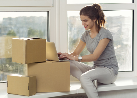 woman  laptop: Beautiful girl moving in the new apartment Stock Photo