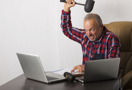 blow: Angry man crashing laptop with a hammer Stock Photo
