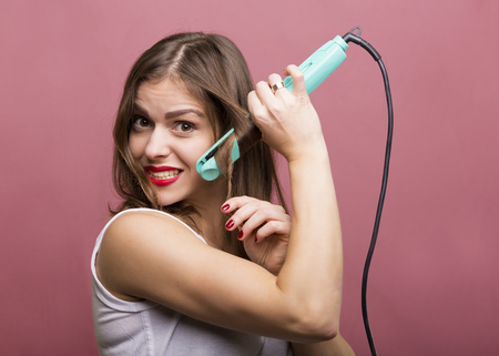 Pretty woman styling her hair with a curling iron