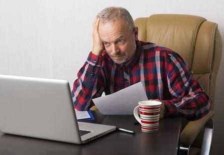 confundido: Hombre que trabaja en la computadora port�til en la oficina