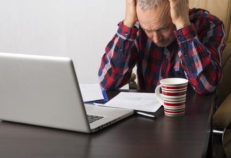 Hombre que trabaja en la computadora portátil en la oficina Foto de archivo - 46799814