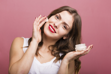Pretty woman holding a bottle with face cream