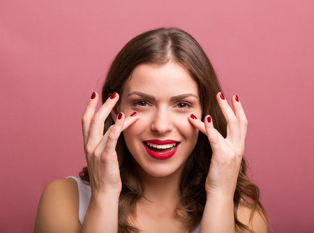 mujer maquillandose: Hermosa mujer joven aplicar una crema de ojos Foto de archivo