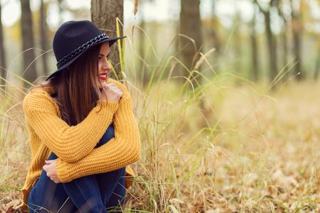 秋の森に座っている孤独な少女 写真素材 - 48094501