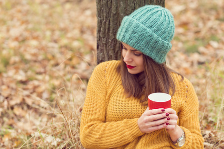lonely tree: Lonely girl enjoying a cup of coffee in the forest