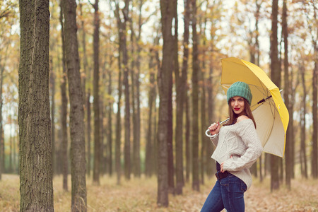 Lonely girl walking in the autumn park with yellow umbrella Archivio Fotografico