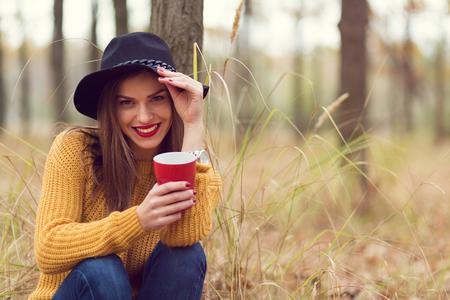 sueteres: Chica solitaria disfrutando de una taza de café en el bosque
