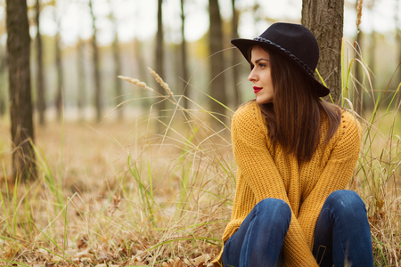 Lonely girl sitting in the autumn forest Stockfoto