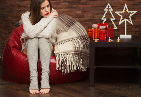 Sad young woman with Christmas presents at her home
