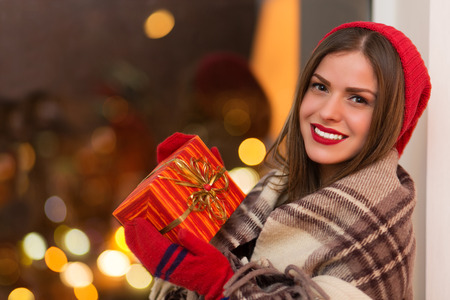 attracive: Happy young woman holding gift box