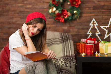 home decorated: Happy young woman with a book at her home decorated for Christmas