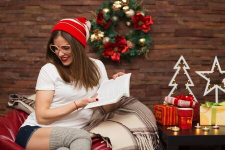 home decorated: Pretty hipster woman reading a book at her home decorated for Christmas