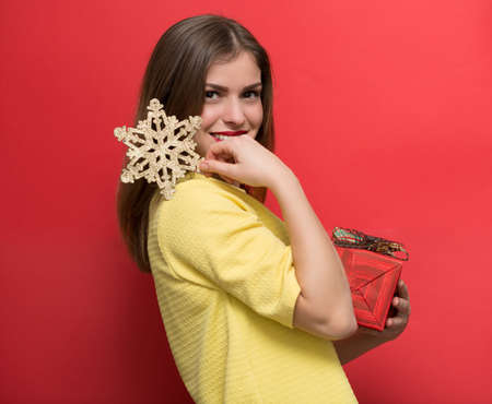 winter fashion: Woman with Christmas present and a golden snowflake