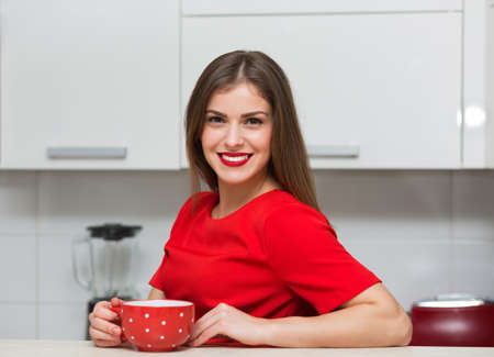 glamorous: Glamorous housewife having a cup of tea at her kitchen Stock Photo