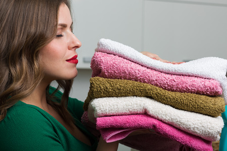 Woman with clean towels, basket and various washing detergents Stockfoto