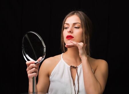 woman mirror: Beautiful woman looking at the round cosmetic mirror Stock Photo