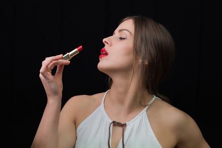 Beautiful woman applying red lipstick
