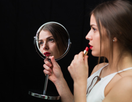 Beautiful Woman Applying Red Lipstick And Holding Mirror Stock Photo