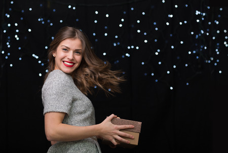 Beautiful woman in a with a gift box on a black background with bokeh