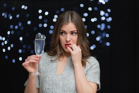 Schöne Frau mit einem Glas Champagner auf einem schwarzen Hintergrund mit Bokeh
