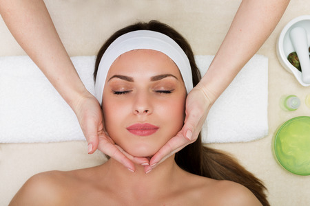 Beautiful woman having a facial massage beauty treatment Stock Photo