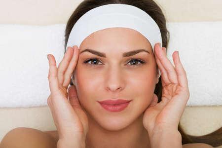 Beautiful woman having a facial massage beauty treatment Imagens